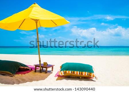 Beach mattress and umbrella on a white sandy beach - stock photo