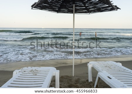 Beach mood/two white beach loungers under a straw umbrella right beside the sea shore and some distant in recognizable persons in the sea at sunset time.