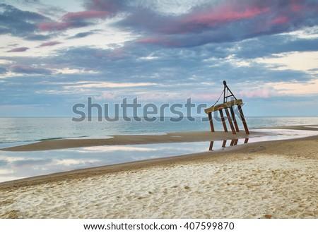 Beach on Baltic Sea shore. Old fishing installation - stock photo