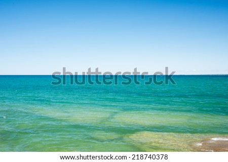 Beach on Lake Ontario near Picton.  Very clear azure blue water.   - stock photo