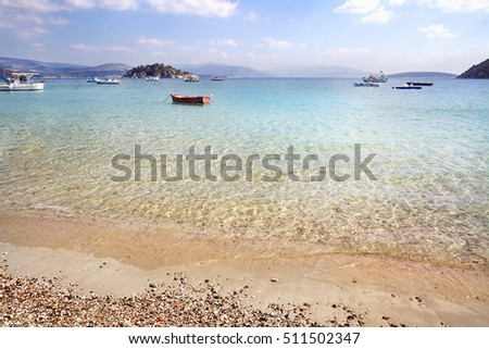 Beach on sea coast and the boats standing in water in the distance, Greece