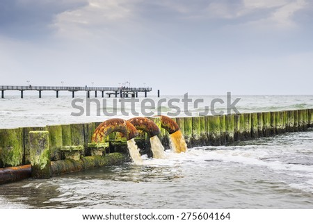 Beach on the Baltic Sea with sewage pipes that pollute the sea - stock photo