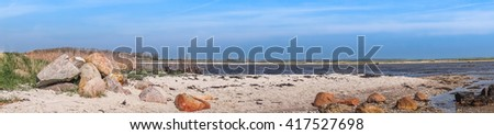 Beach panorama landscape with rocks in the sand - stock photo