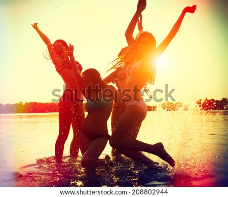 Beach Party. Teenage girls having fun in water. Group of happy young people dancing at the beach on beautiful summer sunset. Silhouettes of group of teen girls jumping and dancing. Joyful friends - stock photo