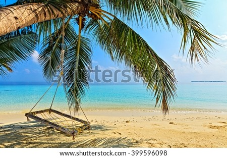 Beach place for relax under the shade of a palm tree - stock photo
