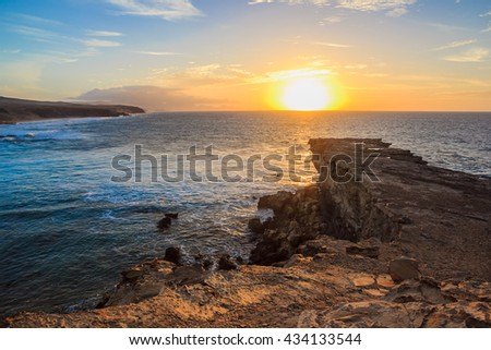 Beach Playa de la Pared. Beautiful scenic sunset over sea. Illimitable ocean, rocky cliff, foamy waves and mountains in a haze. Colorful sun goes down into the dark waters of the ocean. Fuerteventura - stock photo