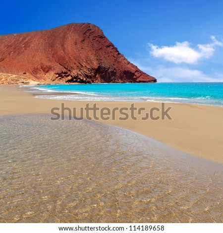 Beach Playa de la Tejita turquoise in Tenerife Canary islands with red mountain - stock photo