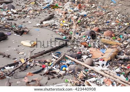 Beach pollution. Plastic bottles and other trash on sea beach of Livingston, Guatemala. (selective center focus)  - stock photo