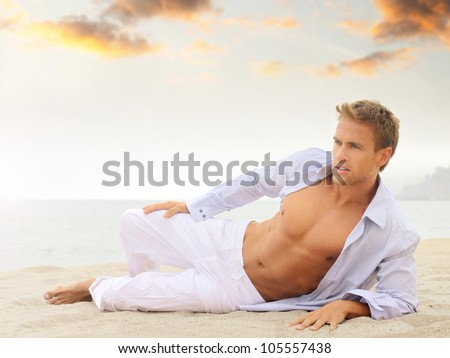 Beach portrait of a good looking young blond man in white pants and light blue shirt laying down looking off