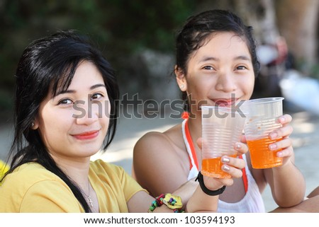 Beach portrait of two ladies holding a plastic cup with orange juice.