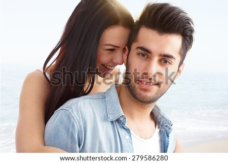 Beach portrait of young attractive loving couple, embracing and smiling happy. - stock photo