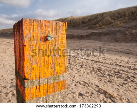 beach post with orange flaking paint carrying a metal marker nail indicating the dutch standard sea level datum point the Amsterdam Ordnance Datum (Normaal Amsterdamse Peil or NAP) with dunes behind - stock photo