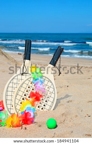 beach rackets with a colorful hawaiian necklace on a golden shore