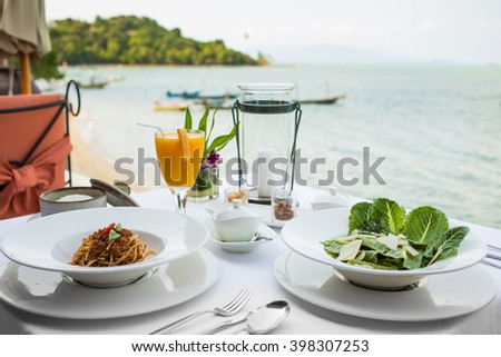 Beach restaurant. Spaghetti Bolognese, pasta with tomato beef sauce, fresh mango juice, green salad with cheese, sea view.