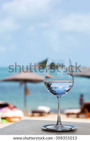 Beach restaurant with sea view, glasses, plates, food, tropical background with sea and sun umbrellas