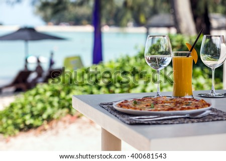 Beach restaurant with sea view, glasses, plates, food, tropical cocktail with mango and pizza Margarita