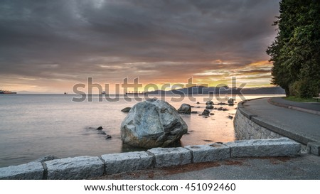 beach rocks and sea wall  in the sunset  - stock photo