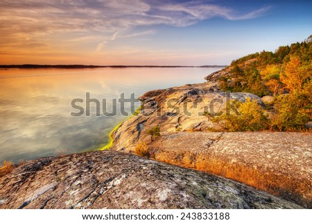 Beach rocks in warm summer evening with still water in Porkkalanniemi , Finland - stock photo