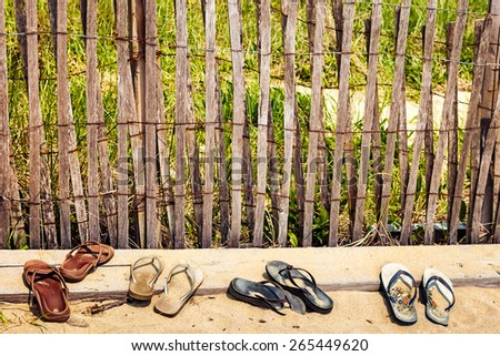 Beach sand dune fence made of wood slats, with a row of old sandals and flip flops at the base. Typical summer beach scene in New England, USA - stock photo