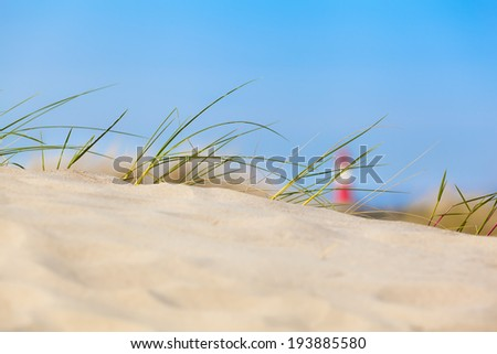 Beach sand dune with grass and a soft focused red and white striped lighthouse at the distance/Sand Dune View - stock photo
