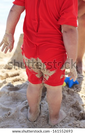 Beach sand on baby swimming suit