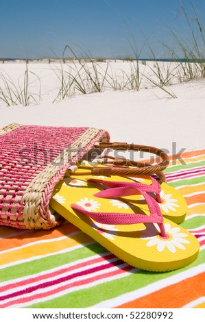 Beach sandals at seashore on towel - stock photo