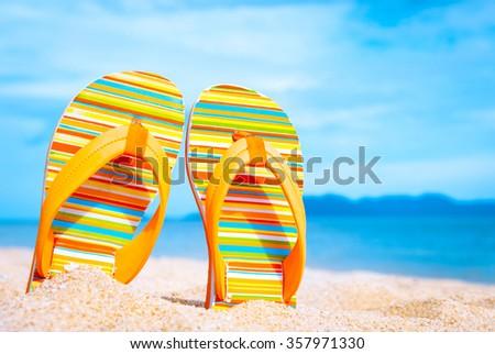 Beach sandals on the sandy coast - stock photo