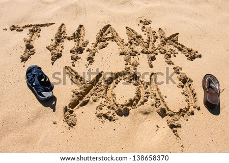 Beach sandals with thank you written in the sand - stock photo
