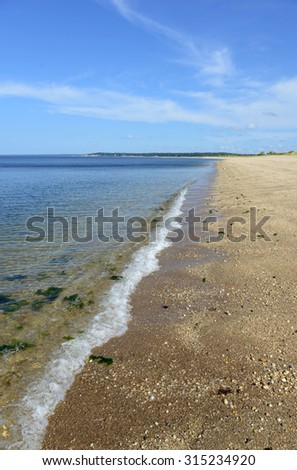 Beach scene on Long Island sound with sand beach and blue sky in the surf zone