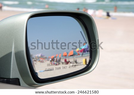 "Beach scene through a rear view mirror.  Focus is on the words ""objects in the mirror are closer than they appear"". - stock photo"