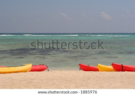 Beach scene with red and yellow kayaks lined up near the water. - stock photo