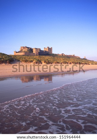 Beach sea and sand dunes at Bamburgh Castle in Northumberland  England - stock photo