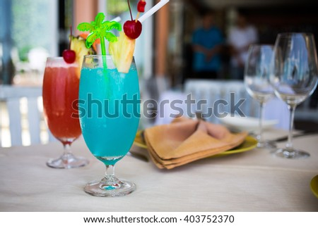 beach sea view restaurant, two cocktails with ice, red and blue - stock photo