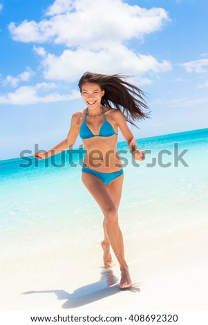 Beach sexy bikini Asian woman having fun coming out of water running laughing playful relaxing on tropical getaway paradise. Young ethnic model with slim weight loss beach body. Summer vacation travel - stock photo