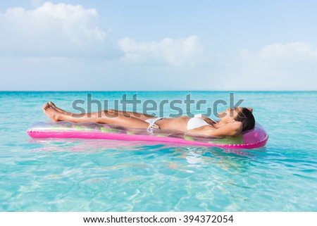 Beach sexy woman relaxing during suntan sunbathing on floating pink pool inflatable plastic air mattress float in pristine turquoise ocean water background at luxury destination getaway. - stock photo