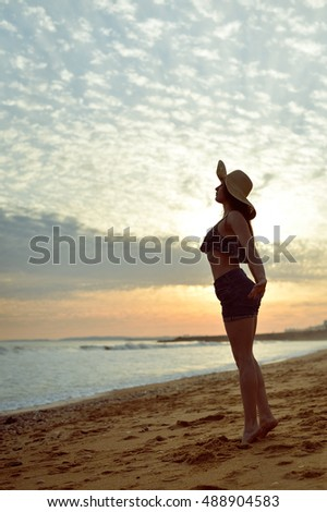 Beach silhouette of the woman dancing during beautiful sun dawn. Natural light and darkness outdoors background
