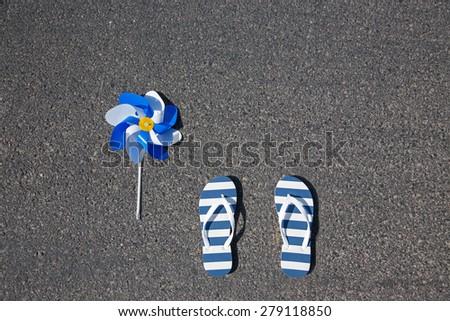Beach slippers with pinwheel lying on asphalt - stock photo