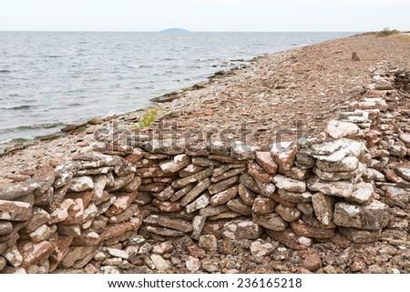 Beach stone wall and sea horizon - stock photo
