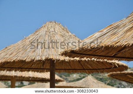 Beach straw parasols and clear blue sky