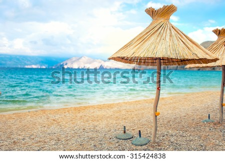 beach straw umbrella lounger chair with sand and clear water. Sea Mediterranean coastline landscape  - stock photo