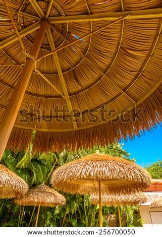Beach straw umbrella on sky background. - stock photo