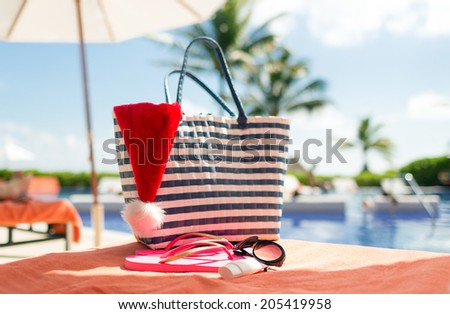 beach, summer, christmas, holidays and vacation concept - close up of santa helper hat, flip-flops, bag, sunscreen and sunglasses at pool - stock photo
