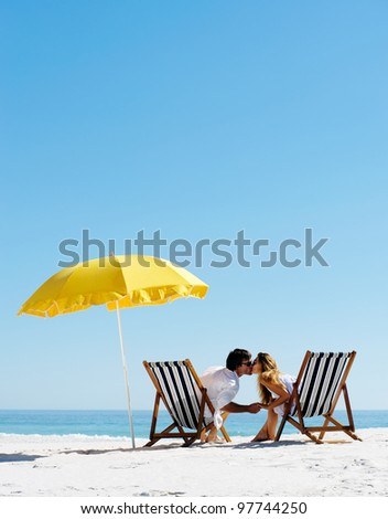 Beach summer couple kissing on island vacation holiday in the sun on their deck chairs under a yellow umbrella. Idyllic travel background. - stock photo