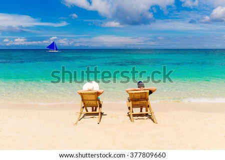 Beach summer couple on island vacation holiday relax in the sun on their deck chairs on the tropical beach. Idyllic travel background. - stock photo
