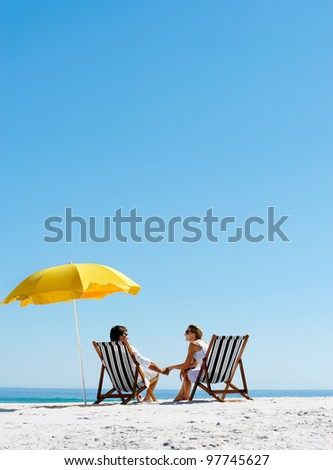 Beach summer couple on island vacation holiday relax in the sun on their deck chairs under a yellow umbrella. Idyllic travel background.