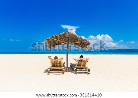 Beach summer couple on island vacation holiday relax in the sun on their deck chairs under umbrella made â??â??of palm leaves. Idyllic travel background. - stock photo