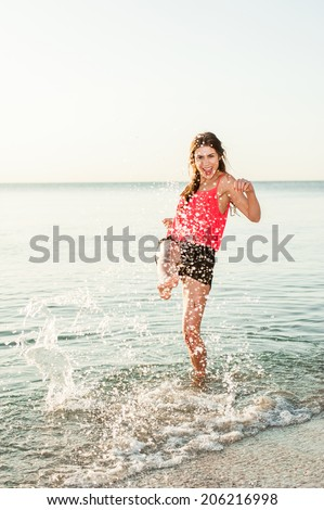 Beach summer fun young woman splashing water, laughing, playing during summer holidays vacation on tropical beach.  - stock photo
