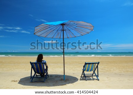 Beach summer girl on island vacation holiday relax in the sun on their deck chairs under a beach umbrella with beautiful blue sky and white cloud