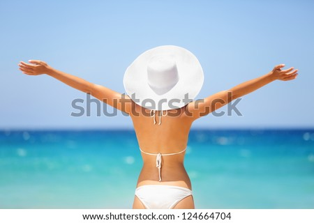 Beach summer holidays woman in happy freedom concept with arms raised out in happiness. Woman model wearing white bikini and beach hat on Big Island, Hawaii. - stock photo