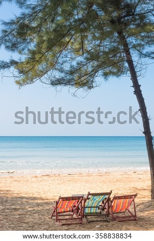 Beach summer on island vacation holiday relax in the sun on their deck chairs under a giant tree. Idyllic travel background. Vacation Sunset Concept - stock photo